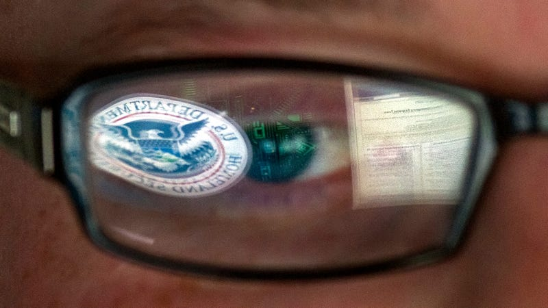 An analyst at the DHS' cyber defense facility in Idaho Falls, Idaho who is supposedly staring at a DHS emblem superimposed on a circuit board graphic for some reason.