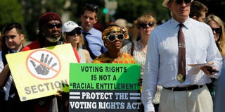 Voting Rights Act supporters listen to the Supreme Court's ruling on Tuesday. (Win McNamee/Getty Images)