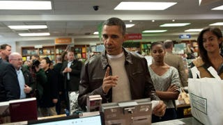 President Barack Obama speaks to a cashier as he pays for books with daughters Malia and Sasha at the Politics & Prose bookstore in Washington, D.C., on Nov. 30, 2013, as part of Small Business Saturday. NICHOLAS KAMM/AFP/Getty Images