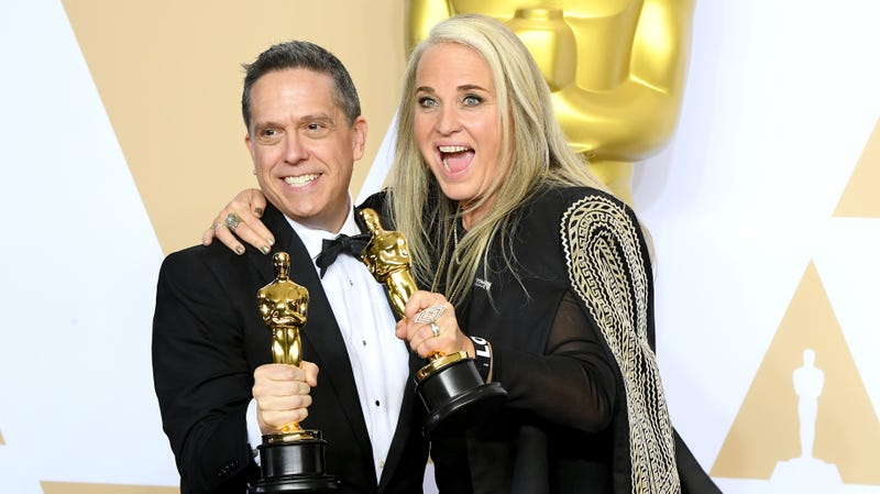 Lee Unkrich and producer Darla K. Anderson, holding their Oscars for Coco.