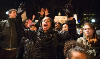 """Protesters in Boston hold up their hands and chant """"Hands up, don't shoot!"""" on Dec. 4, 2014, as they protest the decision by a Staten Island, N.Y., grand jury not to indict a police officer who used a choke hold in the death of Eric Garner in July.Scott Eisen/Getty Images"""