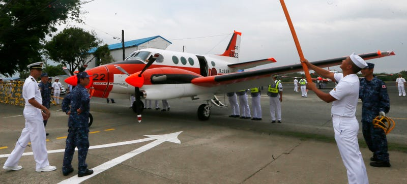 A Philippine Navy personnel paves the way for a Japanese Defense Ministry Beechcraft TC90 training aircraft to park Monday, March 27, 2017 at Naval Air Group in Sangley Point, Cavite province south of Manila, Philippines.(AP Photo/Bullit Marquez)