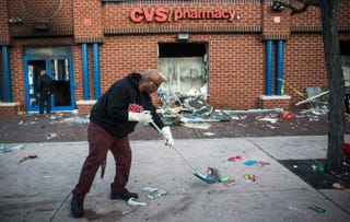 Jerald Miller helps clean up debris April 28, 2015, from a CVS pharmacy in Baltimore that was set on fire during unrest following the funeral of Freddie Gray the day before. The CVS was one of several businesses damaged. Because it's part of corporate chain, it will be rebuilt quickly. The same might not be true for black-owned businesses.Andrew Burton/Getty Images