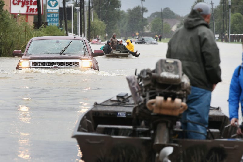Rescue workers and volunteers help residents make their way out of a flooded neighborhood after it was inundated with rainwater following Hurricane Harvey on Aug. 29, 2017, in Houston. (Scott Olson/Getty Images)