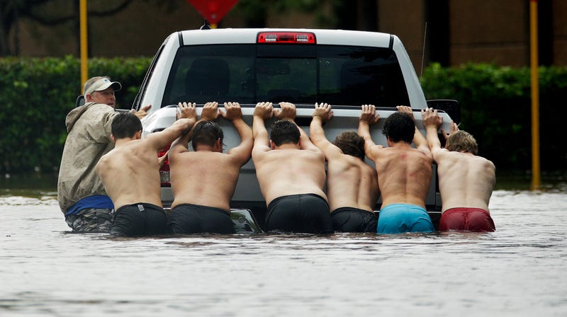 In this Sunday, Aug. 27, 2017 file photo, a group of people push a stalled pickup through a flooded street in Houston, after Tropical Storm Harvey dumped heavy rains.
