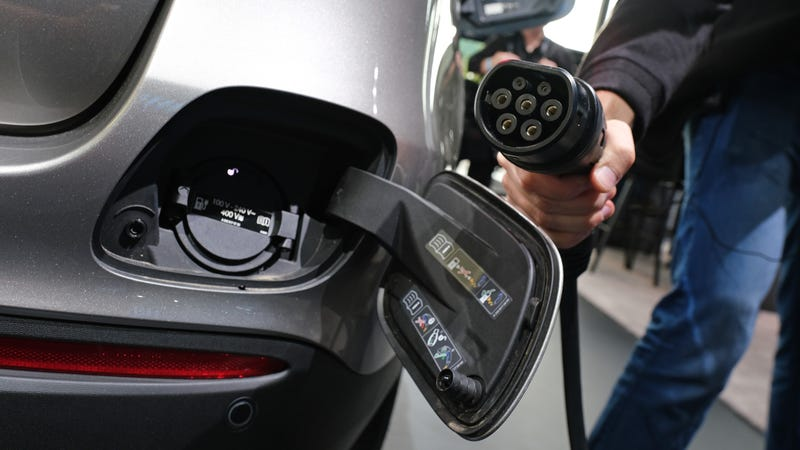 FRANKFURT AM MAIN, GERMANY - SEPTEMBER 09: A journalist holds a charging cable next to the electric charging port as the fuel cap is open behind on a Mercedes-Benz GLC 300e plug-in hybrid at the Mercedes-Benz media preview at the 2019 IAA Frankfurt Auto Show on September 09, 2019 in Frankfurt am Main, Germany. The IAA will be open to the public from September 12 through 22. (Photo by Sean Gallup/Getty Images)