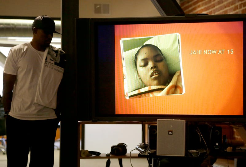 A recent photo of Jahi McMath is shown on a video screen next to her uncle Timothy Whisenton at a news conference in San Francisco on Dec. 23, 2015. (Jeff Chiu/AP)