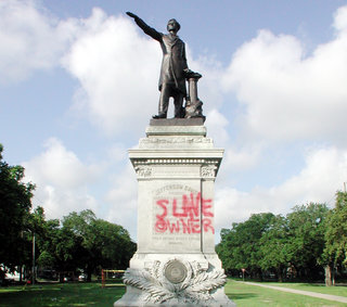 """Monument of Jefferson Davis, who was president of the Confederate States of America, with his true legacy, """"Slave Owner,"""" scrawled across the baseBART EVERSON/CREATIVE COMMONS"""