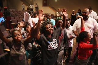 Residents of Ferguson, Mo., shout as the City Council and mayor leave the altar at the Greater Grace Church after the Ferguson City Council meeting on Sept. 9, 2014. The meeting was held at the church to accommodate the large crowd.Scott Olson/Getty Images