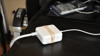 Illustration for article titled Use a Rubber Band to Keep Your Laptop's Power Brick from Slipping Off Your Desk
