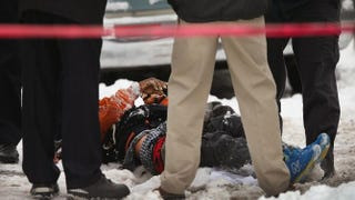 Police investigate a homicide scene after a 24-year-old man was found dead with a gunshot to his back along a sidewalk in the Lawndale neighborhood of Chicago on Dec. 15, 2013.Scott Olson/Getty Images