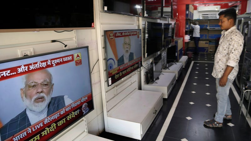 A salesperson watches Indian prime minister Narendra Modi addressing the nation on a television in Mumbai, India, March 27, 2019.