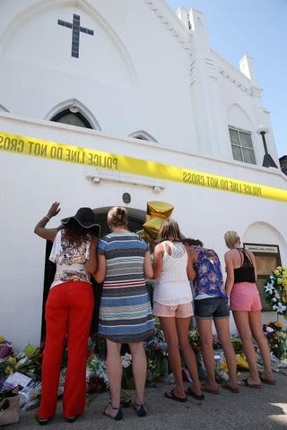 People pray as they pay their respects in front of Emanuel African Methodist Episcopal Church June 18, 2015, in Charleston, S.C.Joe Raedle/Getty Images