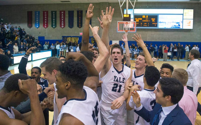 Yale guard Nick Victor (21) and teammates, celebrating their Saturday win against Columbia, raise 4 fingers in reference to recently expelled captain Jack Montague. (Image via Bryan R. Smith/AP)