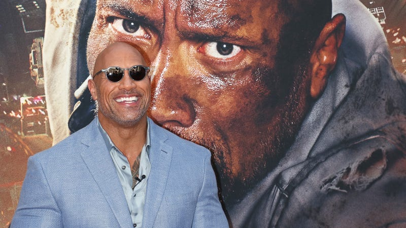 A tiny Dwayne Johnson being stared down by a much bigger Dwayne Johnson.