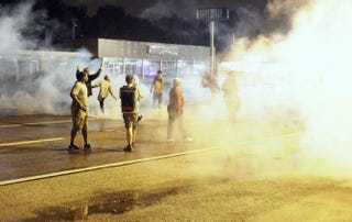 Demonstrators protesting the August 9 police shooting of 18-year-old Michael Brown react as police fire tear gas on the streets of Ferguson, Missouri early on August 17, 2014.  Photo by Joshua LOTT/AFP/Getty Images