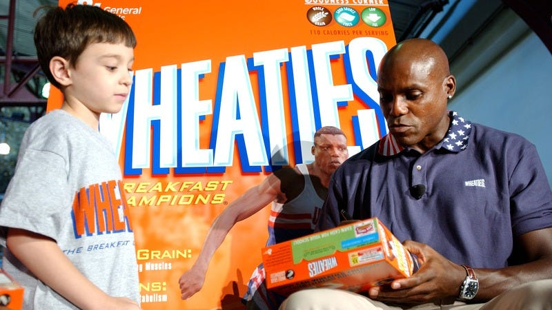 Olympian Carl Lewis autographs his Wheaties box in 2004 in New York (Photo: Stephen Chernin/Getty Images)