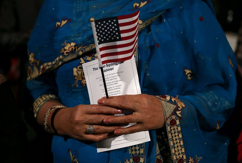 An immigrant holds an American flag as she is sworn in as a U.S. citizen during a naturalization ceremony at the Paramount Theatre on Nov. 18, 2015, in Oakland, Calif.Justin Sullivan/Getty Images