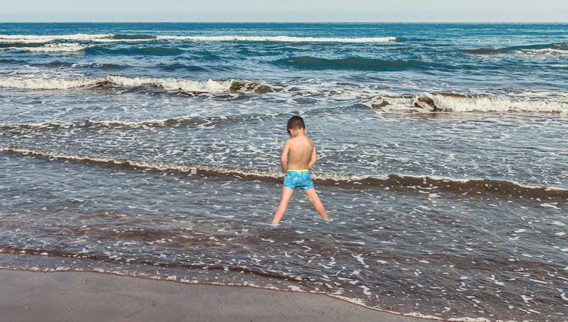 Illustration for article titled Poseidon Incarnate: This Little Boy At The Beach Is Standing At The Shoreline With His Bathing Suit Down Peeing Directly Into The Waves
