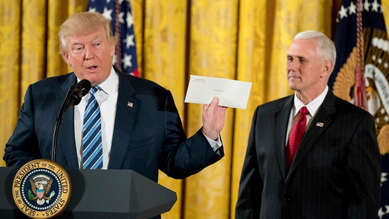 President Trump holding the letter from Barack Obama. Image via the AP.