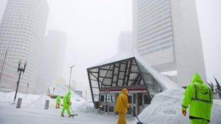 Workers clear snow around the Massachusetts Bay Transportation Authority's South Station Feb. 9, 2015, in Boston.Kayana Szymczak/Getty Images