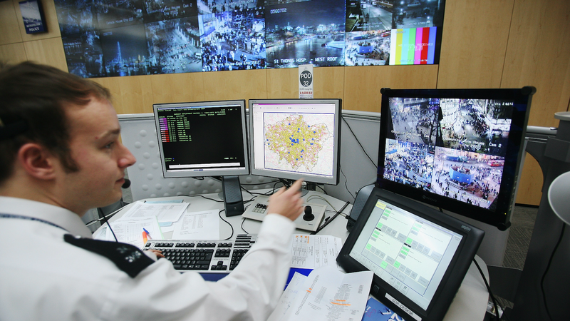 A police officer watches a television monitor displaying a fraction of London's CCTV camera network