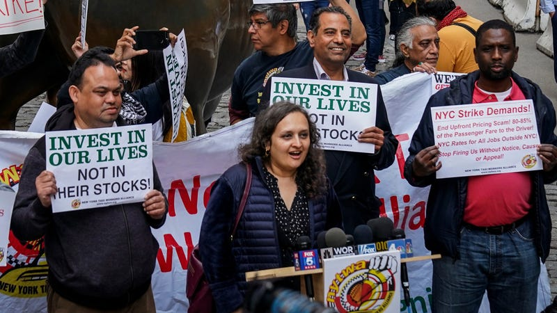 Bhairavi Desai of the New York Taxi Workers Alliance protests Uber and its investors by the Wall Street charging bull
