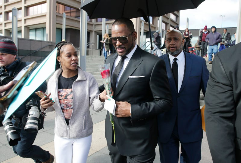 A fan hands singer R. Kelly a rose after his court date at the Leighton Courthouse on March 22, 2019 in Chicago, Illinois. R. Kelly appeared before a judge to request permission to travel to Dubai to work several concerts.