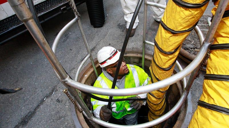 Technician installs new fiber optic cables underground after Hurricane Sandy.