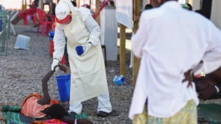 A health worker wearing protective equipment assists an Ebola patient at the Kenema, Sierra Leone, treatment center run by the Red Cross Society Nov. 15, 2014. FRANCISCO LEONG/AFP/Getty Images