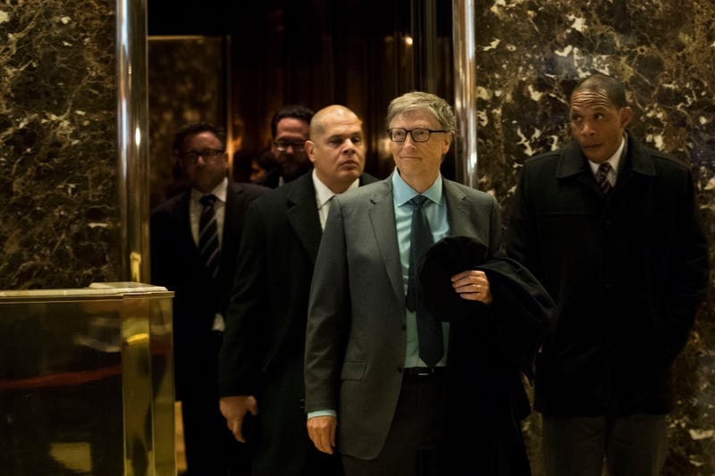 Bill Gates (front, left) exits an elevator before speaking to reporters at Trump Tower in New York City on Dec. 13, 2016.