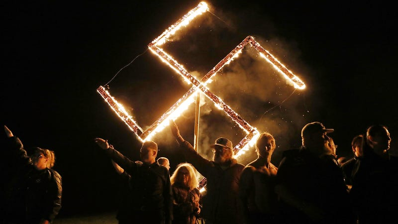 Members of the National Socialist Movement, one of the largest neo-Nazi groups in the U.S., hold a swastika burning after a rally on April 21, 2018, in Draketown, Ga.