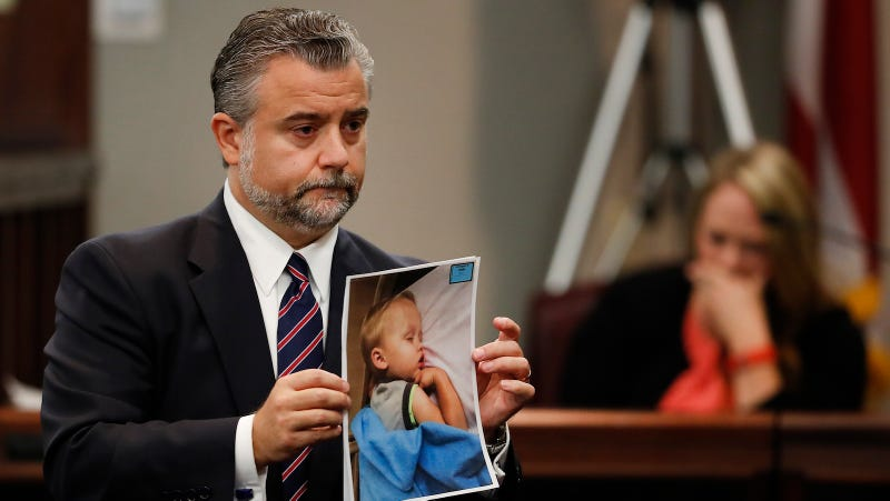 Defense attorney Maddox Kilgore with a photo of the boy. Image via AP.
