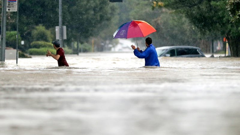 Moses Juarez, left, and Anselmo Padilla wade through floodwaters from Tropical Storm Harvey on Sunday, Aug. 27, 2017, in Houston, Texas. Image via the AP.