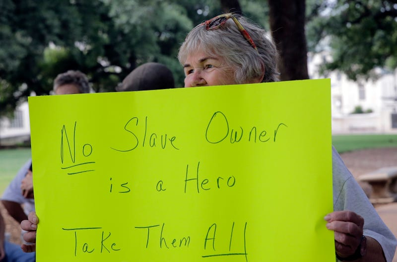 Cindy Beringer holds a sign as she watches a statue of Confederate President Jefferson Davis is moved from its location in front of the school's main tower the University of Texas campus, Sunday, Aug. 30, 2015, in Austin, Texas.