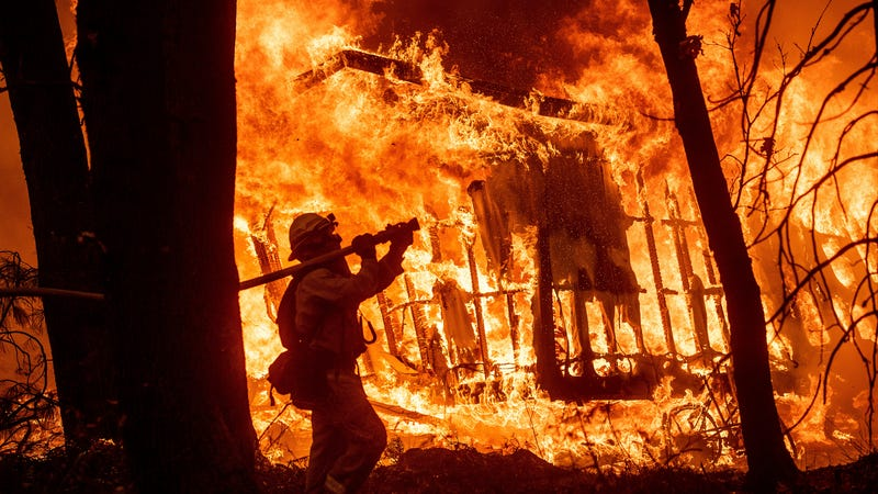 Firefighter Jose Corona sprays water as flames consume from the Camp Fire consume a home in Magalia, Calif., on Friday, Nov. 9, 2018.