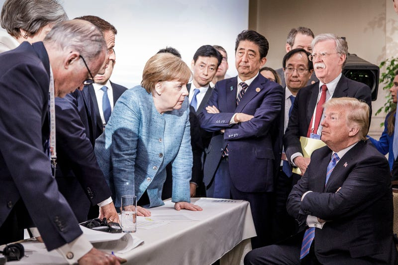 German Chancellor Angela Merkel deliberates with President Donald Trump (seated) during the second day of the G-7 summit on June 9, 2018, in Charlevoix, Canada.