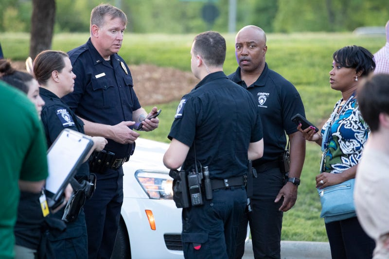 People gather across from the campus of UNC Charlotte after a shooting incident at the school Tuesday, April 30, 2019, in Charlotte, N.C.