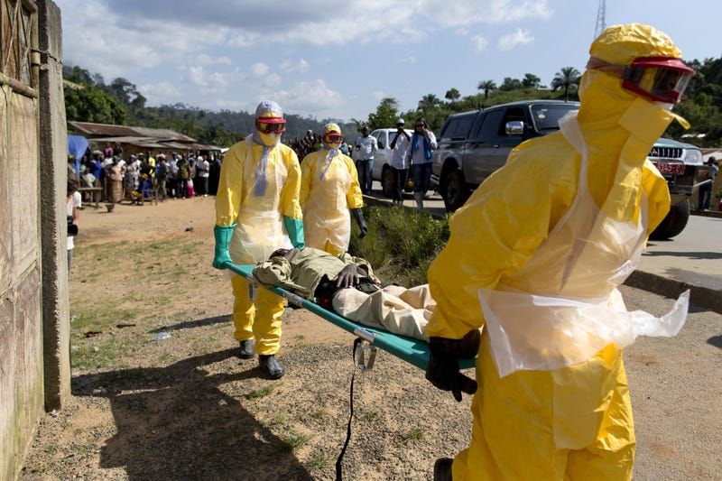 Health workers wearing protective suits carry a patient suspected of having Ebola on their way to an Ebola treatment center run by the French Red Cross in Macenta, Guinea, on Nov. 21, 2014. KENZO TRIBOUILLARD/AFP/Getty Images