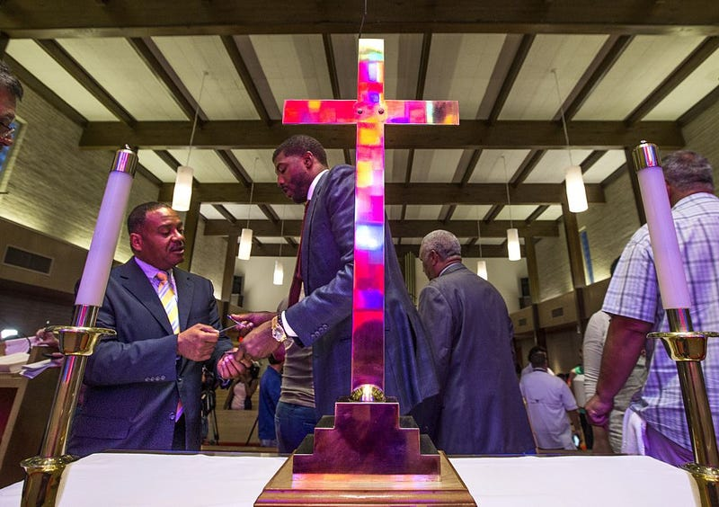 The stained glass windows reflect in a cross as Together Baton Rouge member Joe Connelly (left) networks after his group's press conference about the federal investigation into the shooting of Alton Sterling at the Wesley United Methodist Church in downtown Baton Rouge, La., on July 7, 2016.Mark Wallheiser/Getty Images
