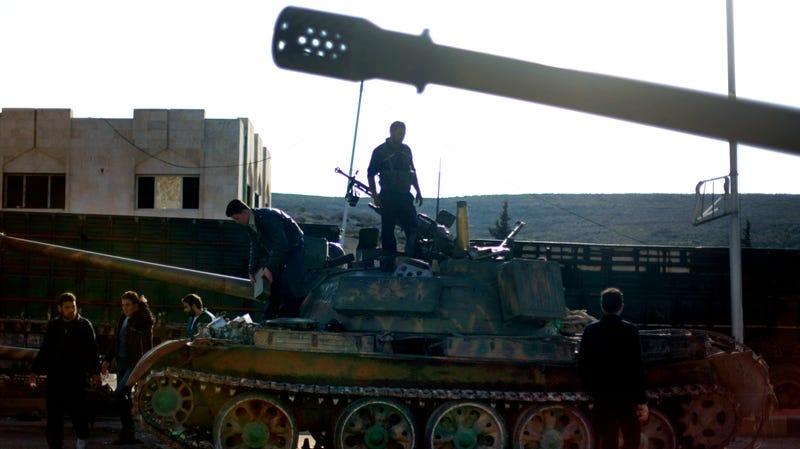 Syrian fighters stand on a tank captured during a raid on a military base near Aleppo, 2012.