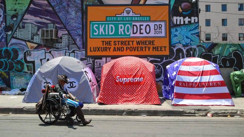 """In May 2019, British artist Chemical X's art installation """"Skid Rodeo Drive"""" highlighted the economic disparities in Los Angeles, where scores of homeless people live in tent communities not far from luxe enclaves like the famed Rodeo Drive. In the L.A. suburb of Pacoima, Calif., dozens of predominantly African-American people are living in tents under the Ronald Reagan Freeway."""