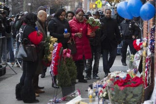 Emerald Garner (center left, holding blue candle), daughter of Eric Garner, visits a makeshift memorial near the site where two New York City police officers were slain.Yahoo Screenshot
