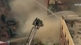 Firefighters work to put out the blaze left in the wake of a gas explosion in New York City's East Harlem neighborhood, March 12, 2014.YouTube screenshot