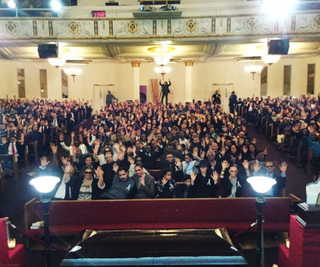 "Sarah Glover, president of the National Association of Black Journalists, looked at mourners at Harlem's First Corinthian Baptist Church Feb. 8, 2016, and asked, ""Who here has been impacted by our saint, Michael J. Feeney? Raise your hand."" She followed up with, ""If you have you been deeply inspired by Michael, raise your other hand."" Then she snapped this photograph.Sarah Glover"