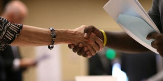 A job seeker shakes hands with a recruiter at a job fair in California. (Justin Sullivan/Getty Images)