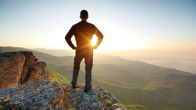 A man on a mountain looking out at a sunset.