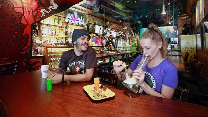 Two customers smoke weed with a bong at the New Amsterdam Cafe in Vancouver, British Columbia on June 20, 2018