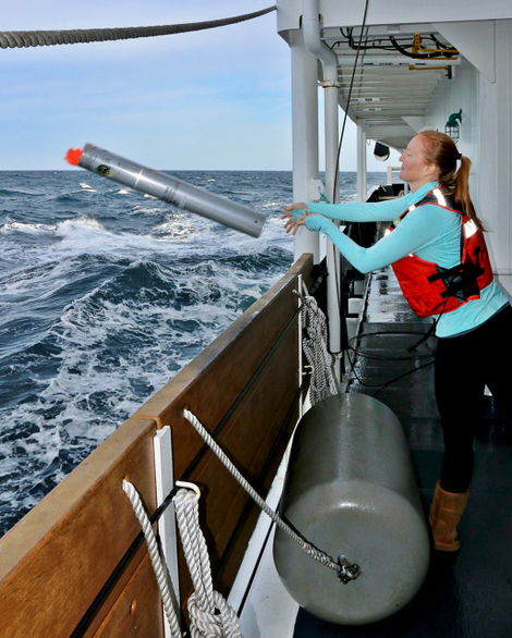 Marine biologist Jessica Crance throws a sonobuoy into the ocean to acoustically monitor for North Pacific right whale calls.