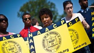 Members of the NAACP hold signs in front of the U.S. Supreme Court in Washington, D.C., on June 25, 2013, after the court struck down a key part of the Voting Rights Act in Shelby v. Holder.NICHOLAS KAMM/AFP/Getty Images